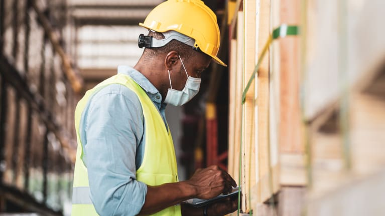 worker wearing a protective face mask in warehouse