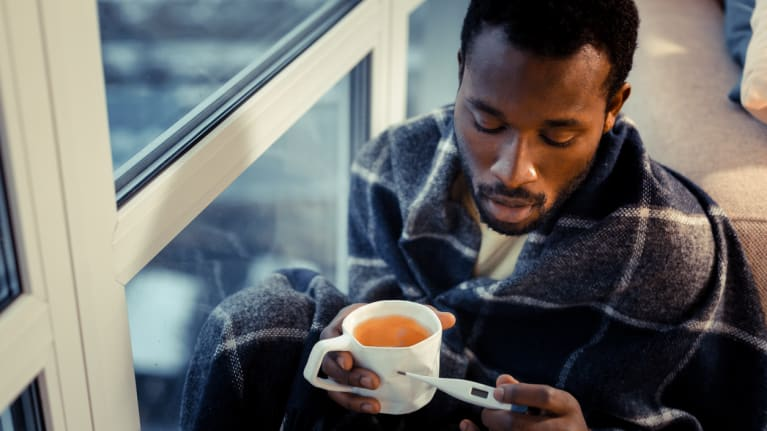 man taking temperature and drinking tea
