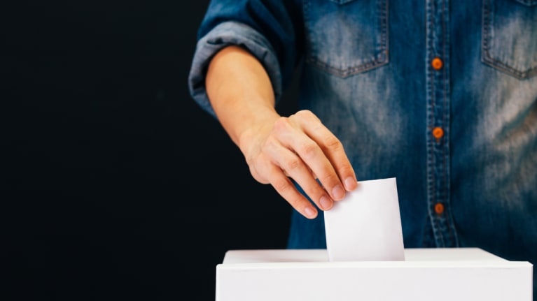 someone casting their ballot in a ballot box
