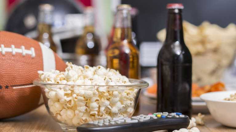 a football, popcorn, remote control and beer