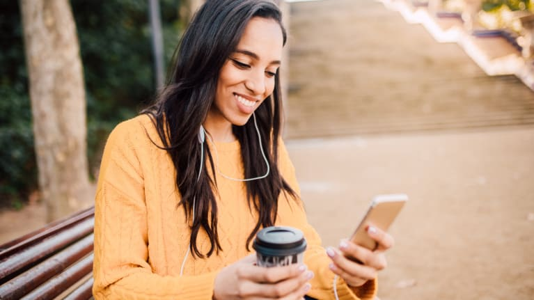 woman holding phone listening to podcast