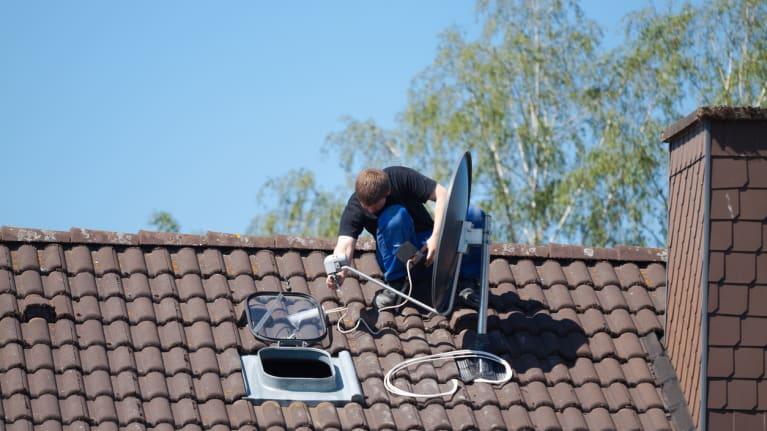 Man installing satellite dish on roof