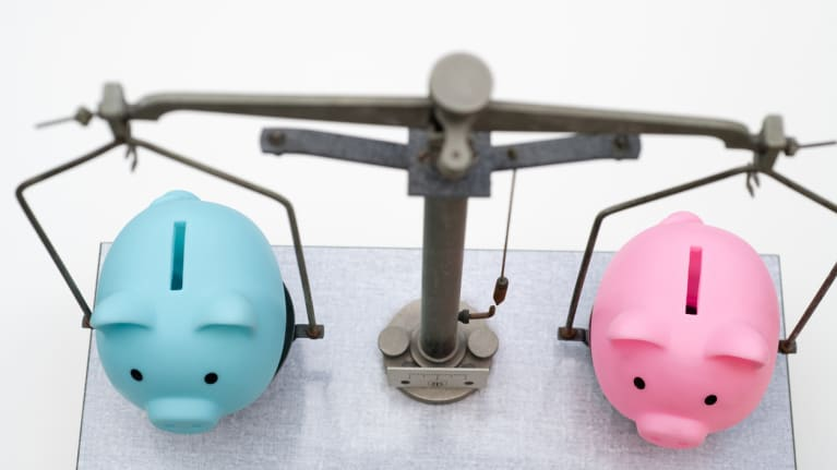 a scale with a blue piggy pank on one side and pink piggy bank on the other