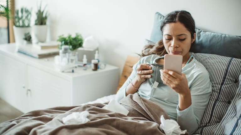 woman sick in bed with tea and smart phone