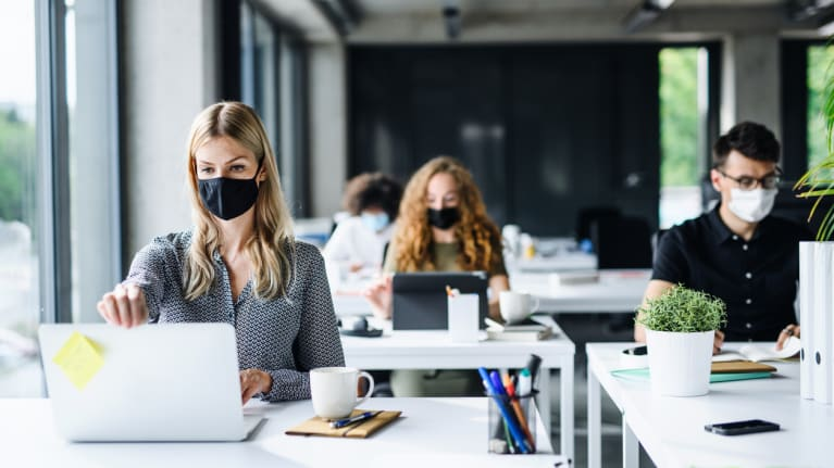 Office workers wearing masks and social distancing