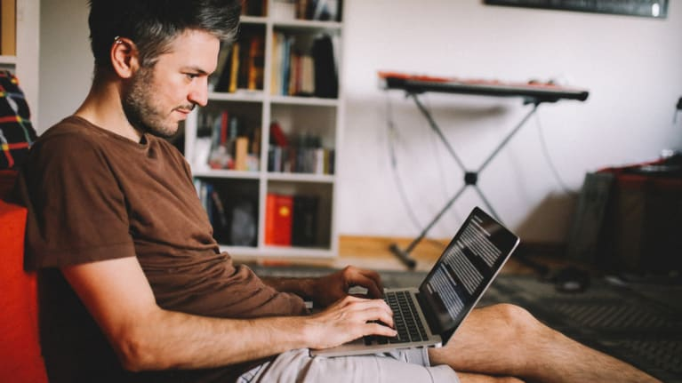 a telecommuting man in a T shirt and shorts working on his laptop