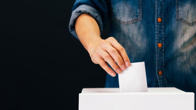 someone casting a paper ballot