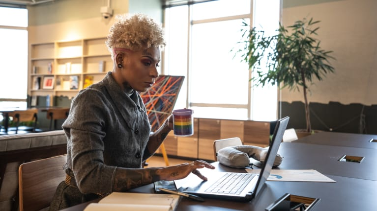 businesswoman working on a laptop and drinking from mug with rainbow colors