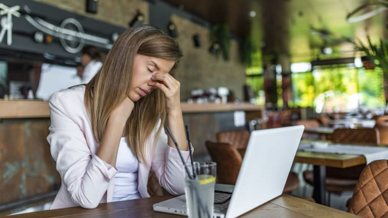 stressed woman working on laptop in empty restaurant