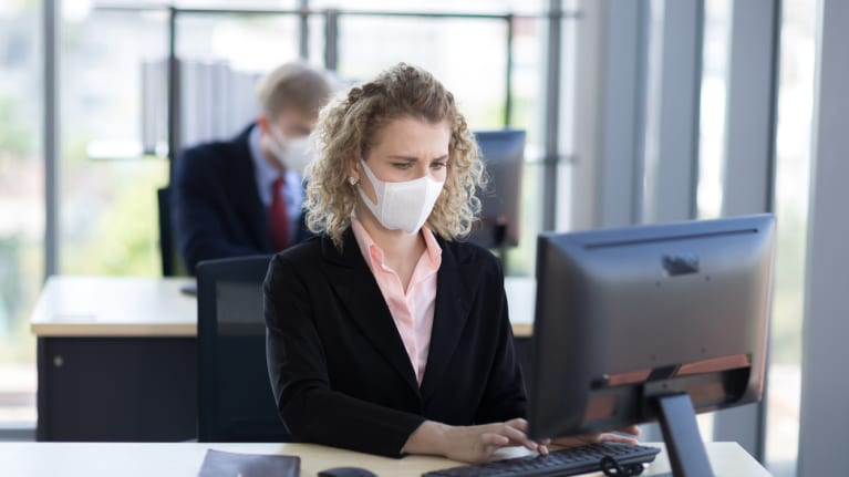 masked employees in office setting