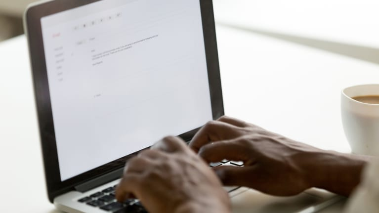 businessman typing e-mail on laptop