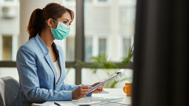 Businesswoman wearing face mask in the office
