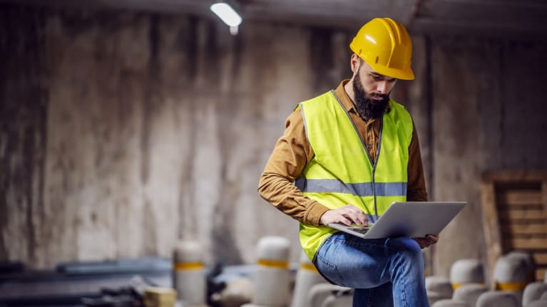 construction project manager wearing vest and hard hat using laptop