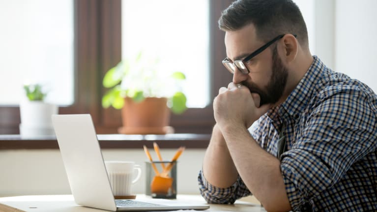 stressed worker looking at laptop