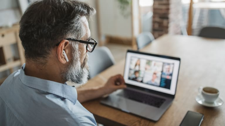 man attending webcast on laptop