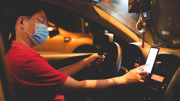 ride-hailing driver wearing face mask using smartphone