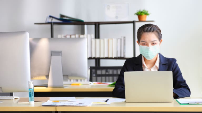 woman at computer in office setting with face mask