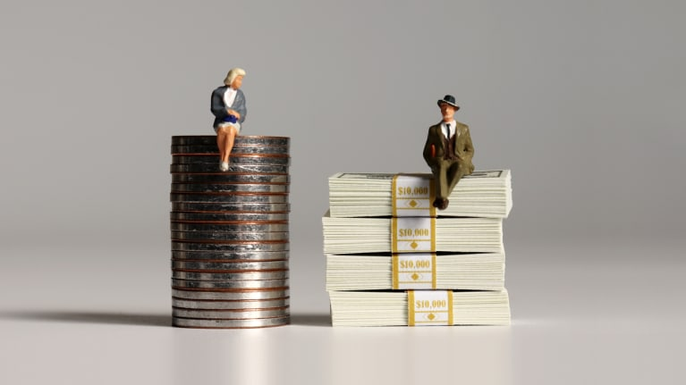 woman figure on stack of coins while man figure is on a stack of bills
