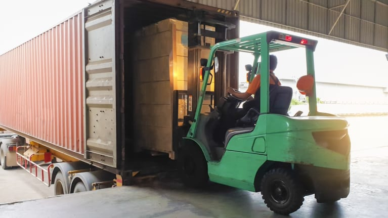Forklift driver unloading goods from a truck