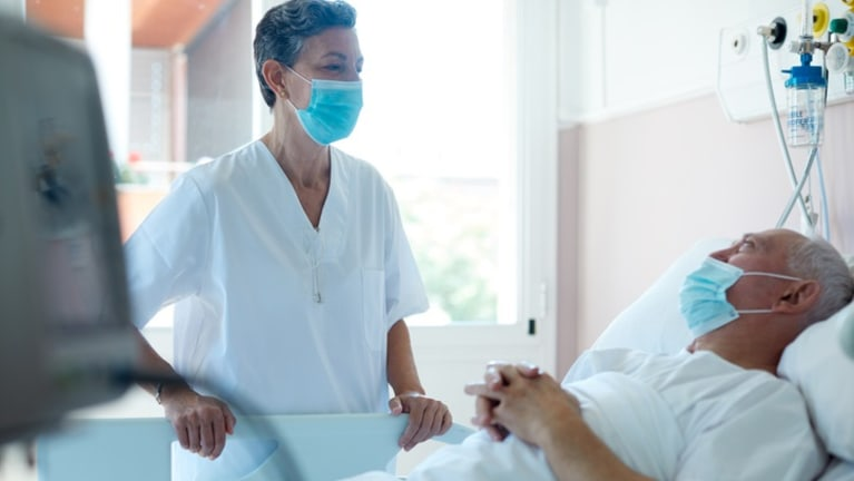 Doctor attending a patient in hospital bed, both wearing masks.
