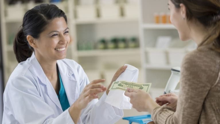 Woman paying cash to purchase medications at pharmacy.