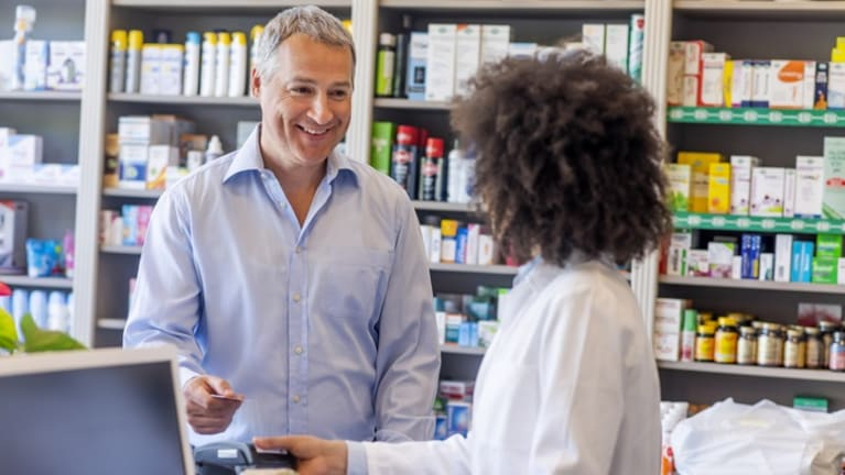 man buying prescription drugs at counter