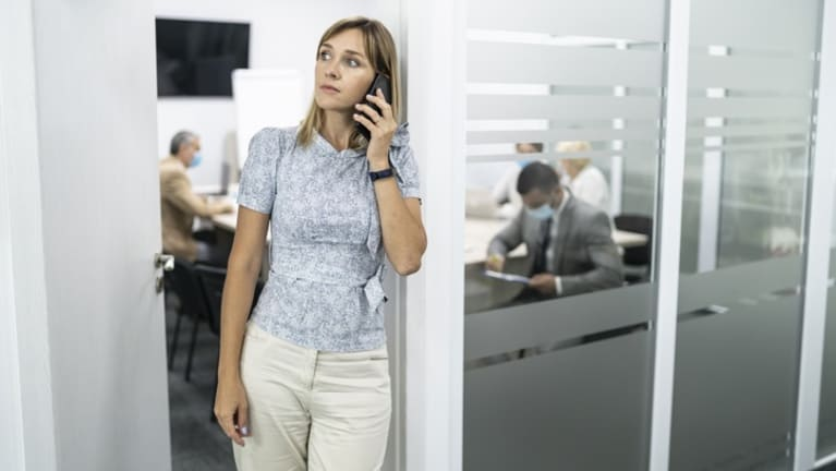 Worried-loooking woman on phone at work, surrounded by employees wearing masks.