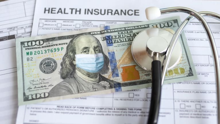 Health insurance papers and dollars.