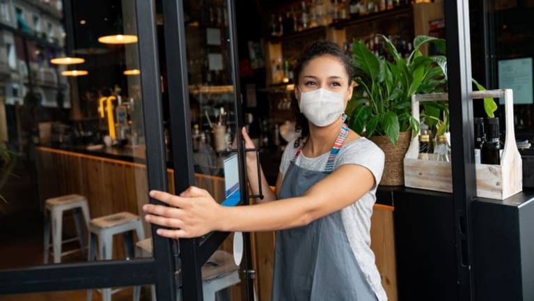 Woman wearing mask reopening her restaurant.