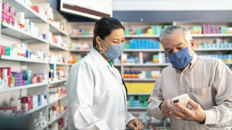 Man discussing price of drug with pharmacist.