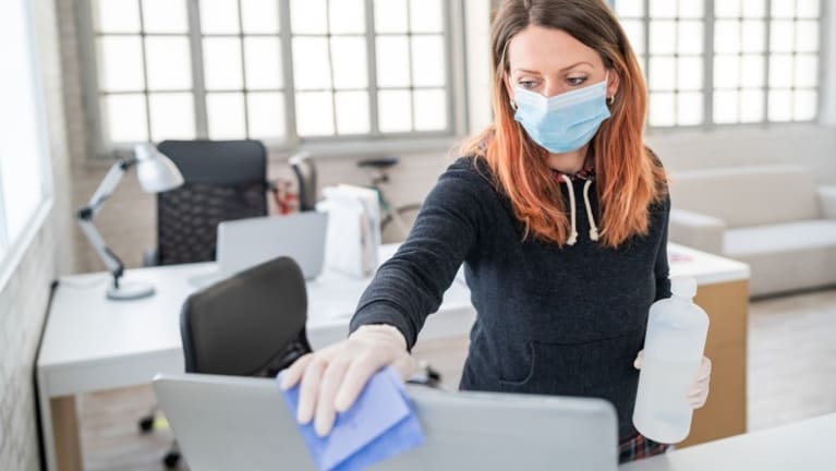 Masked office worker cleans her workspace with disinfectant.