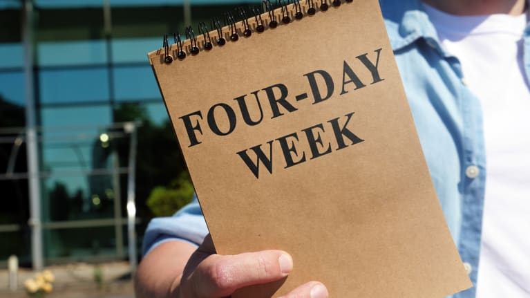 a worker holding a notebook that says four-day week on its cover
