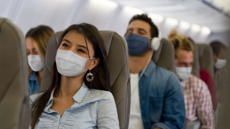 masked airplane travelers during the pandemic