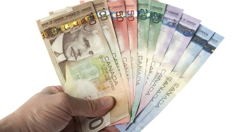 Canadian currency held in someone's hand