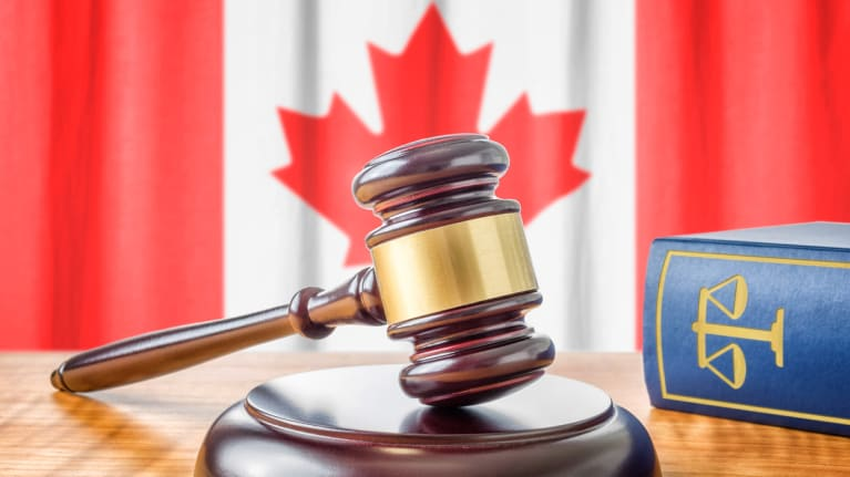 a gavel and law book in the foreground and Canadian flag in the background
