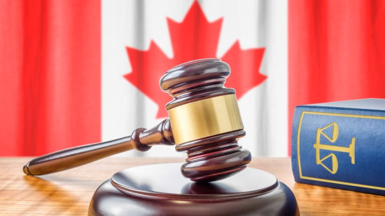 a gavel beside a lawbook and before the Canadian flag