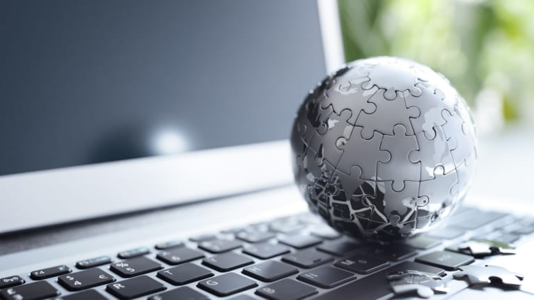 a laptop with a model of a globe on the keyboard