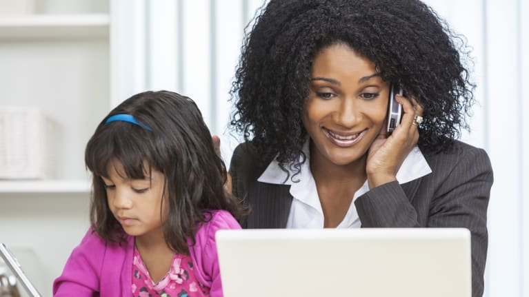 mom on phone and laptop with daughter