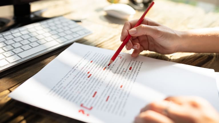 person proofreading with red pen