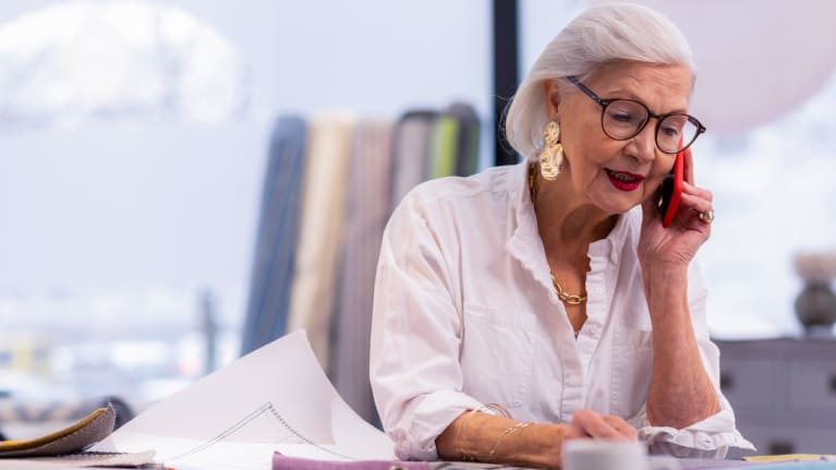 older woman professional at her desk and on the phone