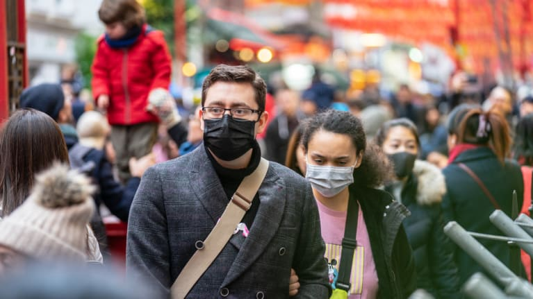 people on the streeet wearing face masks