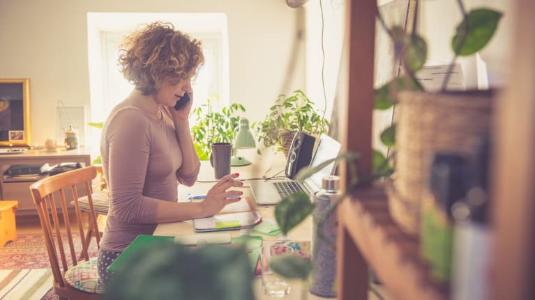 a telecommuting woman at her laptop with house plants in foreground and background